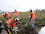 Migranti volontari pulizia marciapiedi